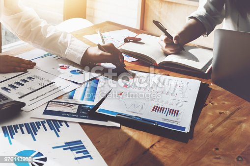 950986656istockphoto business consulting or finance budget plan, business advisor holding pen pointing to explain method profit with business owner use pen write to notebook and use laptop computer. 976443986