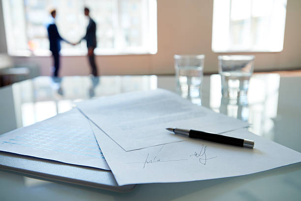 Business contract Signed business contract lying on table, business partners shaking hands in the background signing stock pictures, royalty-free photos & images