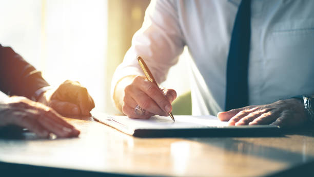 Business contract signing. Closeup Businessman signing a contract investment professional document agreement on the table with pen. agreement stock pictures, royalty-free photos & images