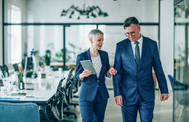 Business conversation Shot of a businesswoman and businessman talking in the work place business suit stock pictures, royalty-free photos & images