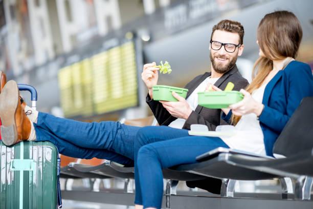 business-paar am flughafen - mittagspause schild stock-fotos und bilder