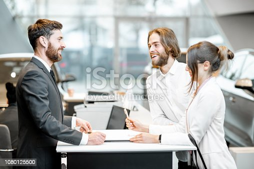 939005154 istock photo Business couple at the stand with salesperson in the showroom 1080125500
