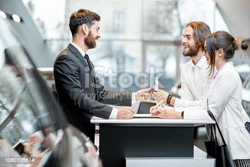 939005154 istock photo Business couple at the stand with salesperson in the showroom 1080125514