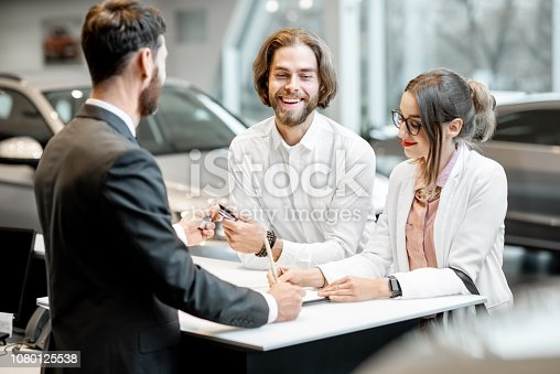 939005154 istock photo Business couple at the stand with salesperson in the showroom 1080125538