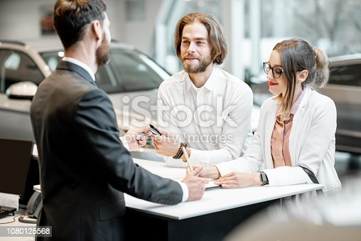 939005154 istock photo Business couple at the stand with salesperson in the showroom 1080125568