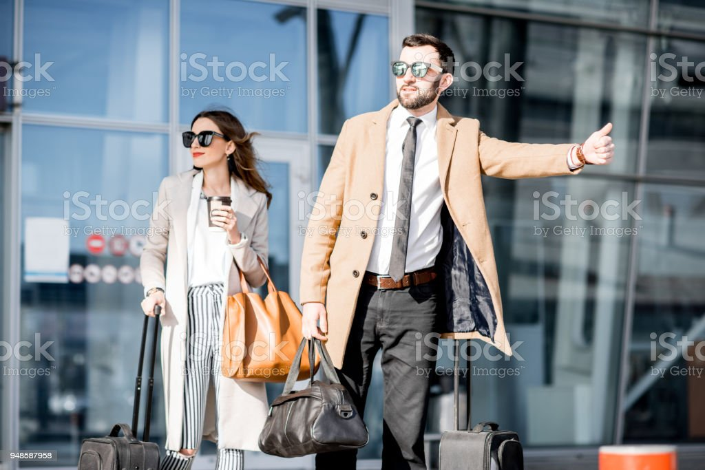 Business couple catching a taxi stock photo