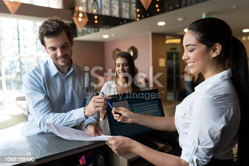 istock Business couple checking in at hotel and man filling a form that receptionist is handing him very happy 1068158490