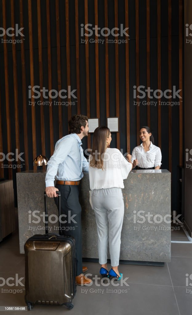 Business Couple Checking Into Hotel At The Front Desk Of A ...