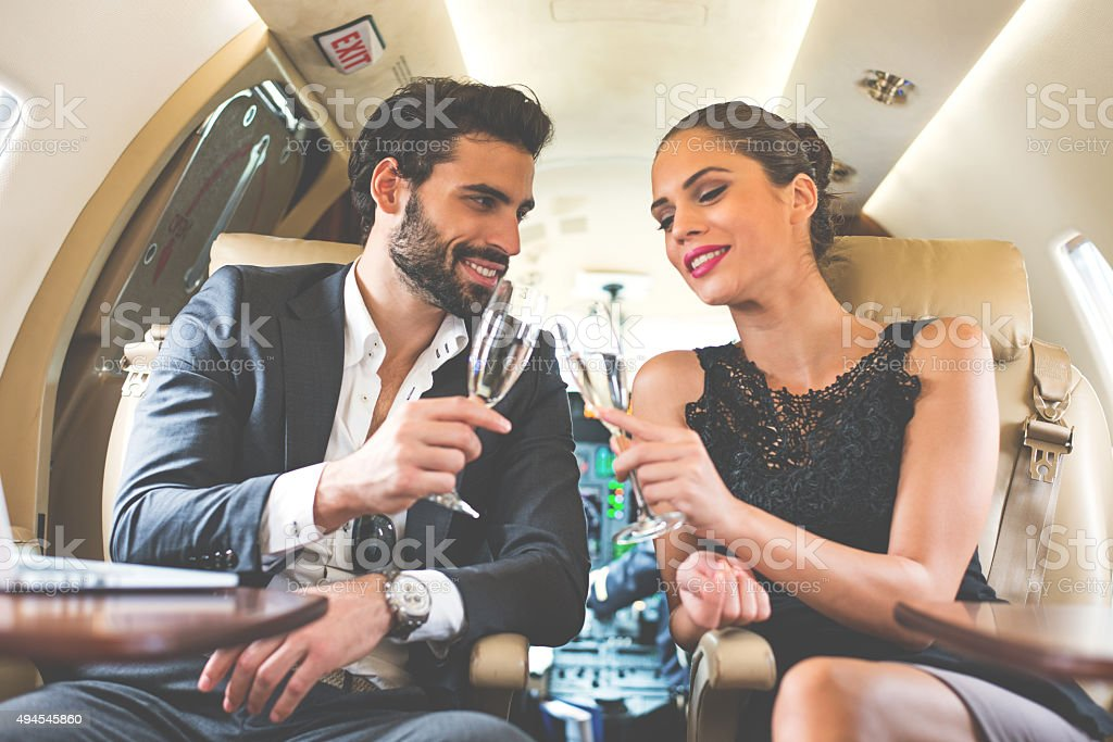 Business couple drinking champagne in private aeroplane stock photo