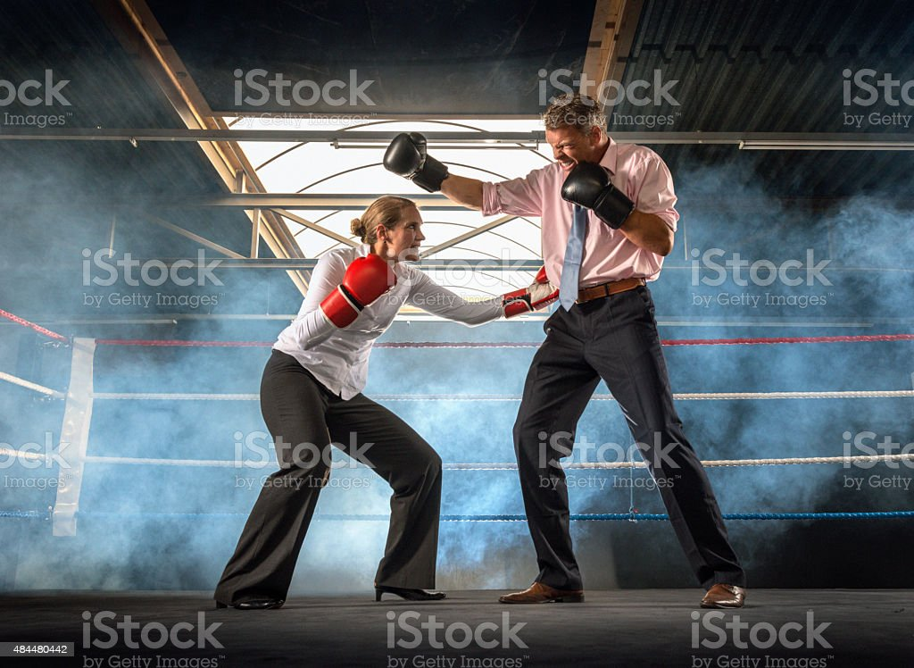 Business couple fighting in smokey boxing ring stock photo