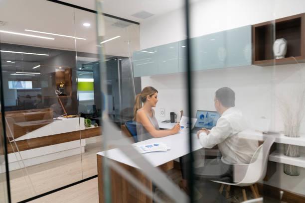 business-paar in einer besprechung über einige dokumente, die auf der suche konzentrierte sich - geführtes lesen stock-fotos und bilder