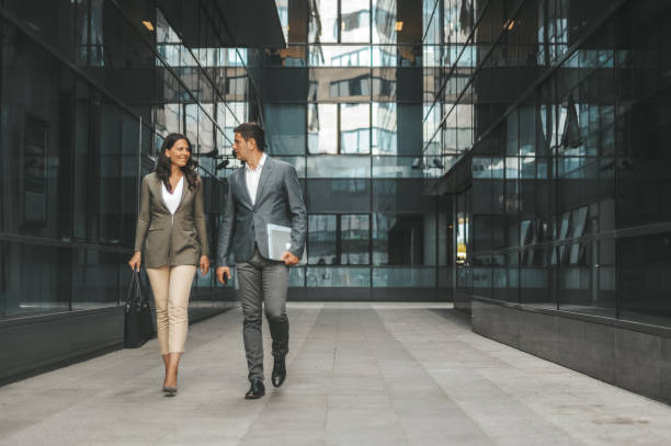 Business couple in front of the office building stock photo