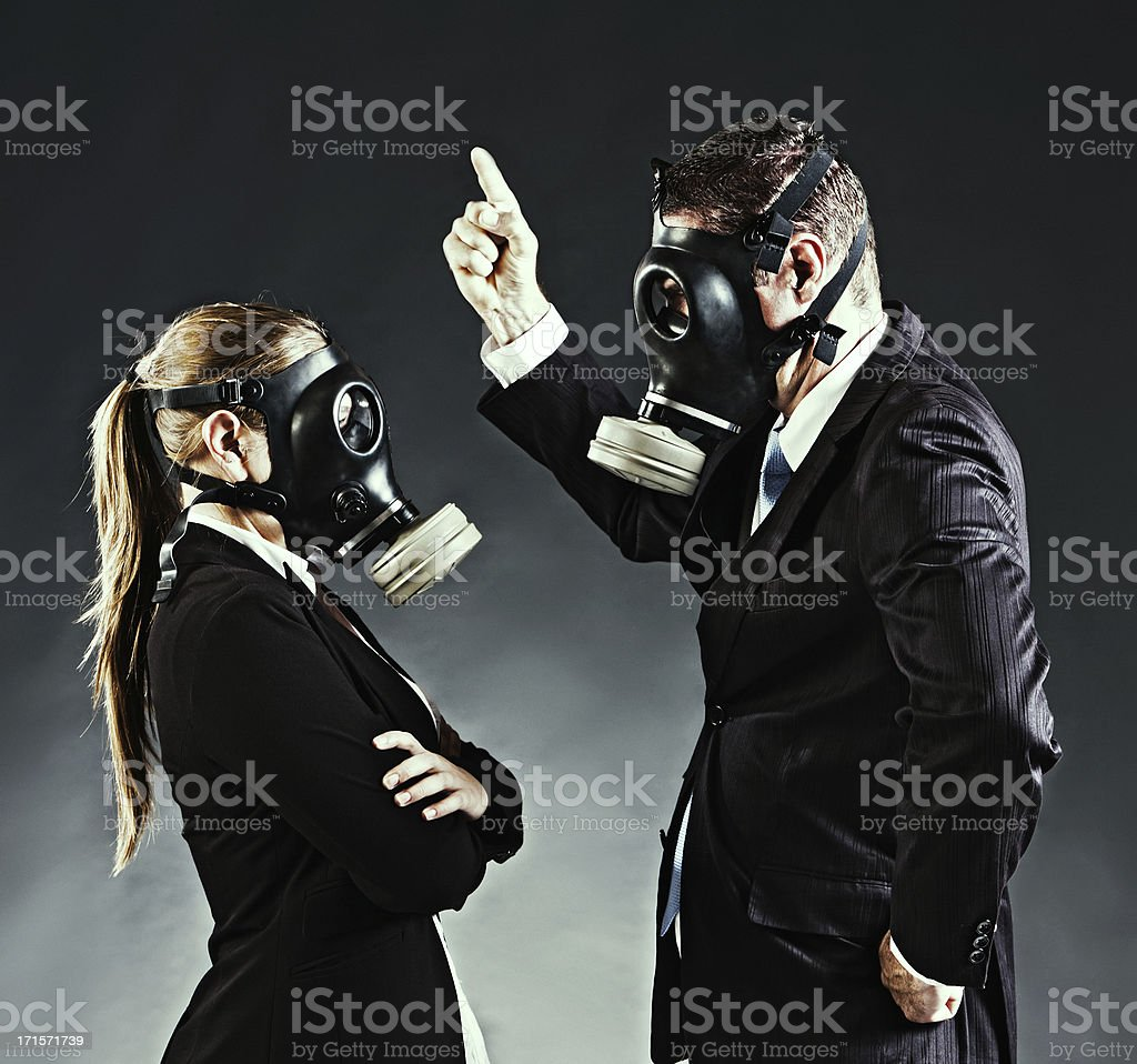 Business couple in gas masks have an argument royalty-free stock photo