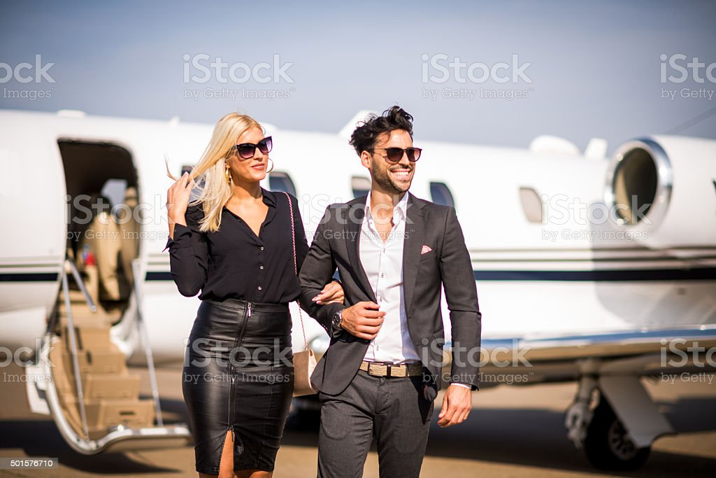 Business couple leaving private aeroplane in the background stock photo