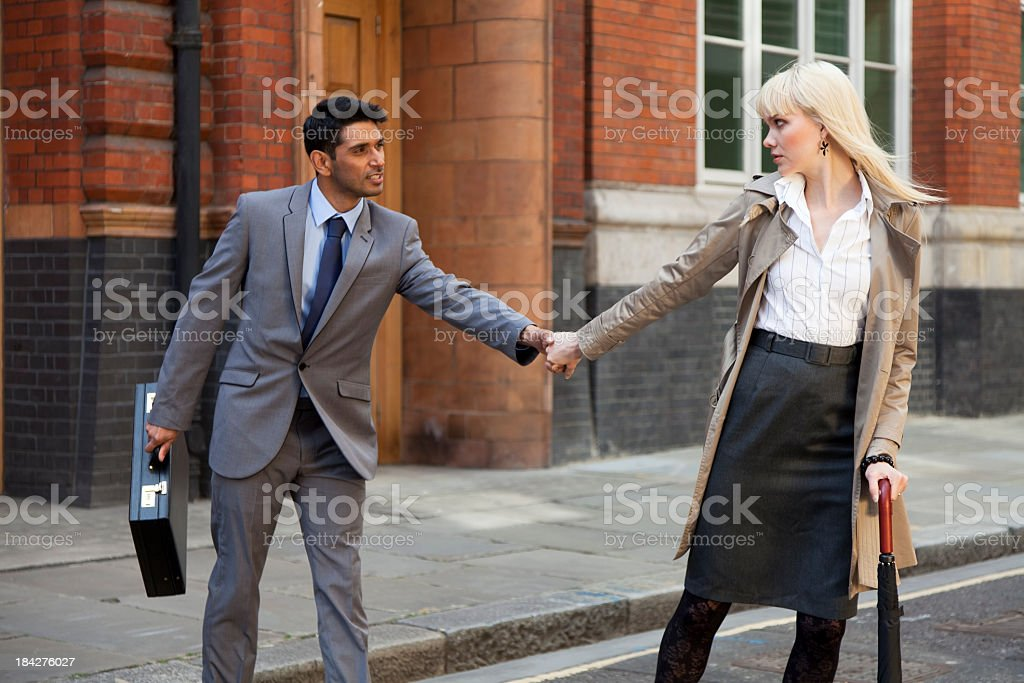 Business Couple On The Road Holding Hands Pulling Eachother royalty-free stock photo