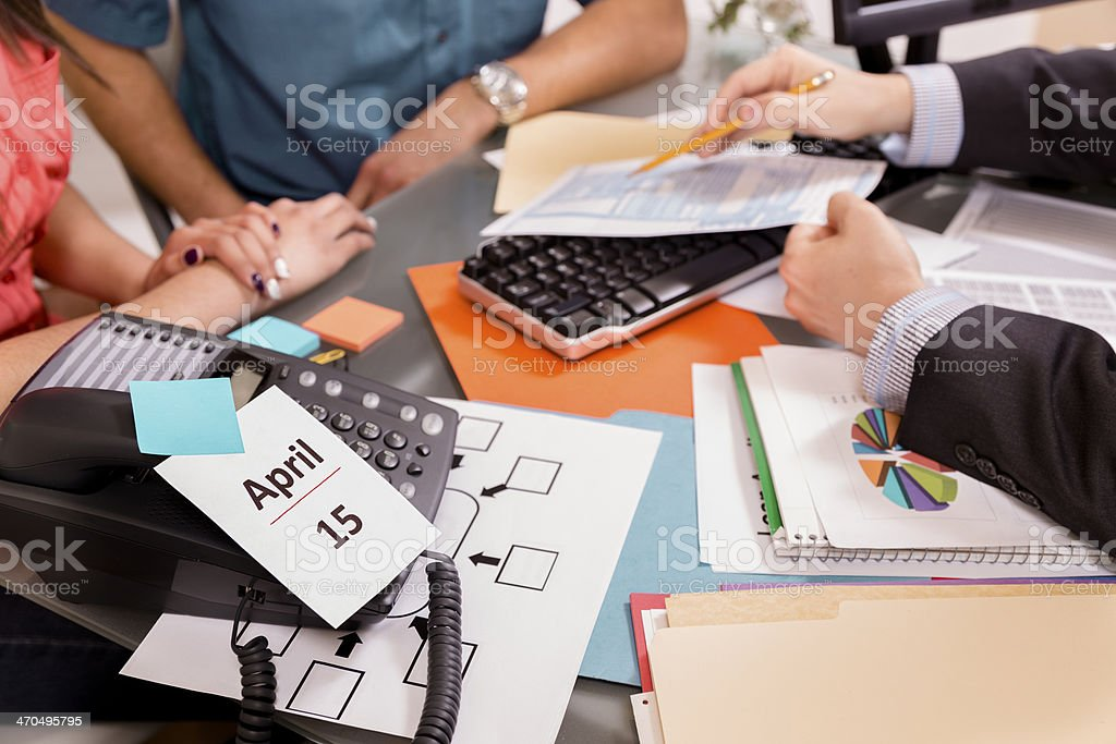 Business Couple Reviews Income Tax Documents With Accountant