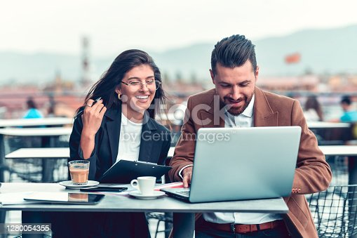 Business Couple Smiling While Working Together On Balcony