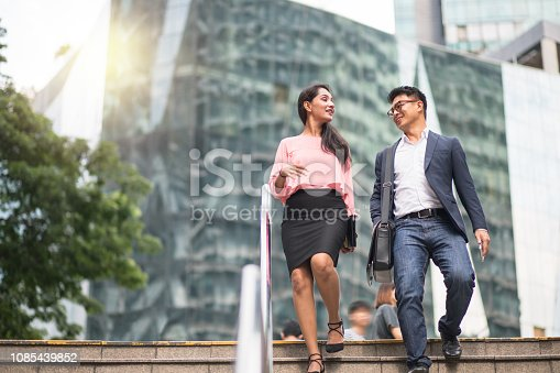 Mid adult business couple talking while walking downstairs. Male and female entrepreneurs are on their way to work. They are wearing smart casuals in city.