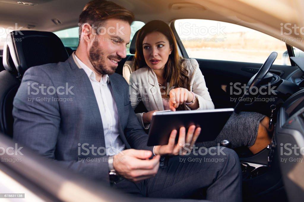Couple d'entreprise à l'aide de tablette numérique dans la voiture photo libre de droits