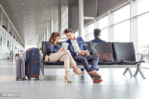 istock Business couple waiting for flight at airport lounge 621690274