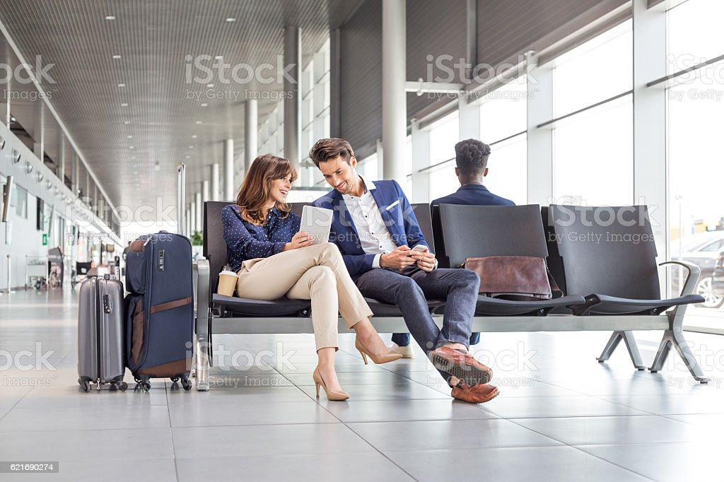 Business couple waiting for flight at airport lounge stock photo