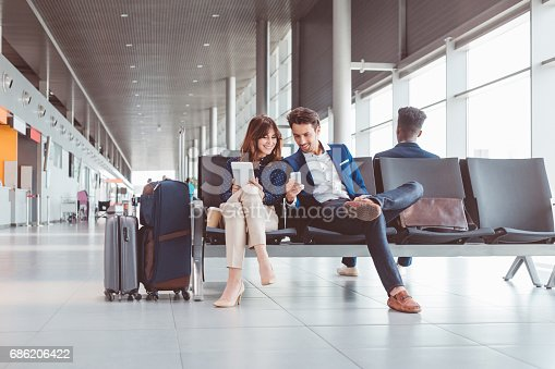 istock Business couple waiting for flight at airport lounge 686206422
