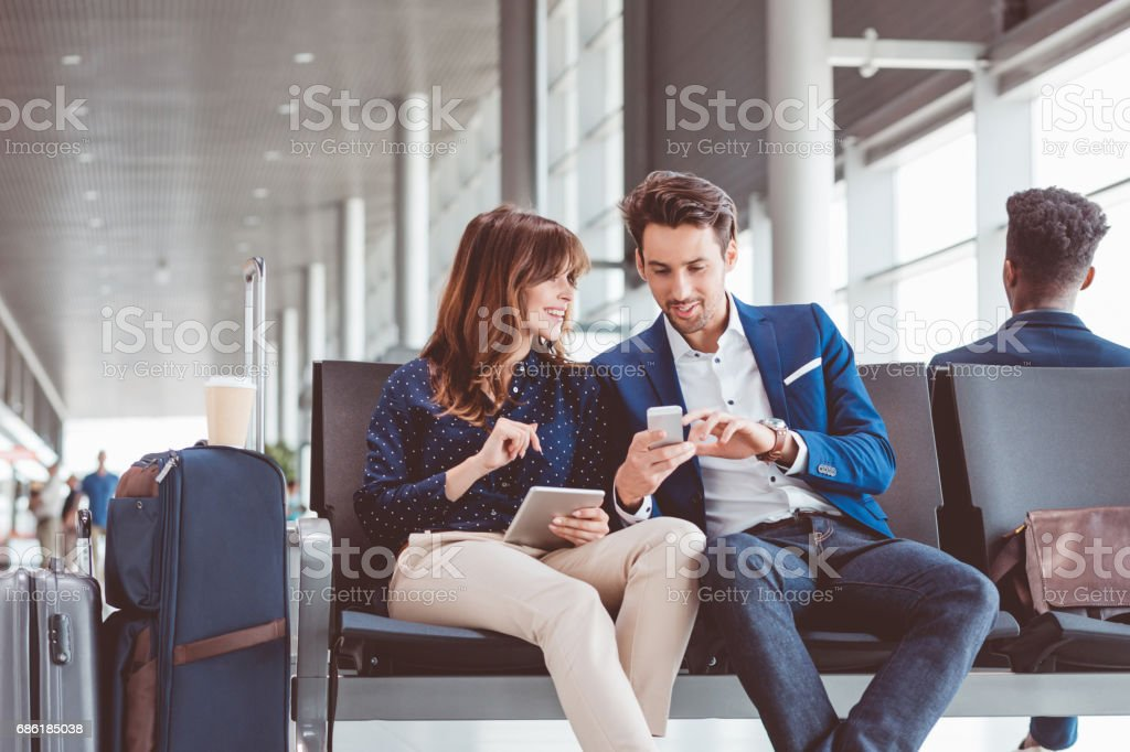 Business couple waiting in airport terminal for flight stock photo
