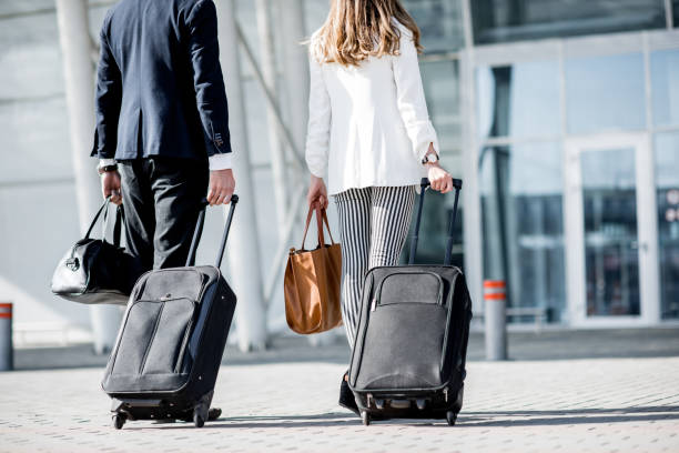 business couple walking to the airport - business travel stock photos and pictures