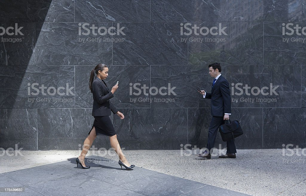 Business couple with cell phones walking on a city sidewalk royalty-free stock photo
