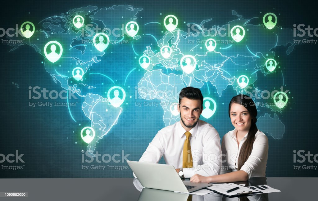 Business couple sitting at table with social media connection symbols...