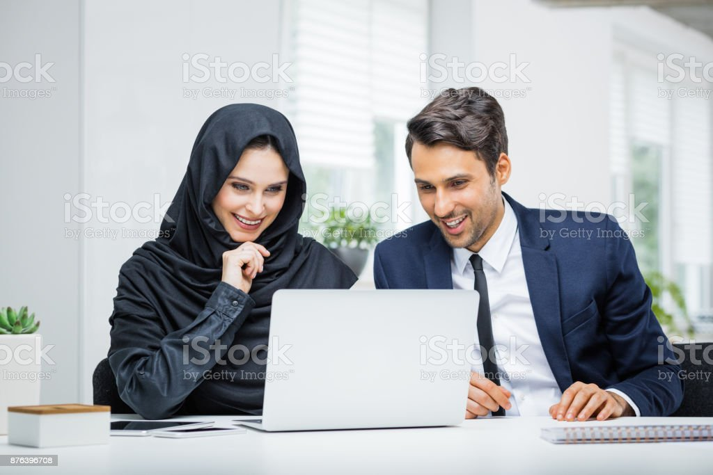 Business couple working together on project at startup office Business couple working together on project at startup office. Musilm businesswoman in hijab with male colleague looking at laptop and smiling. 20-29 Years Stock Photo