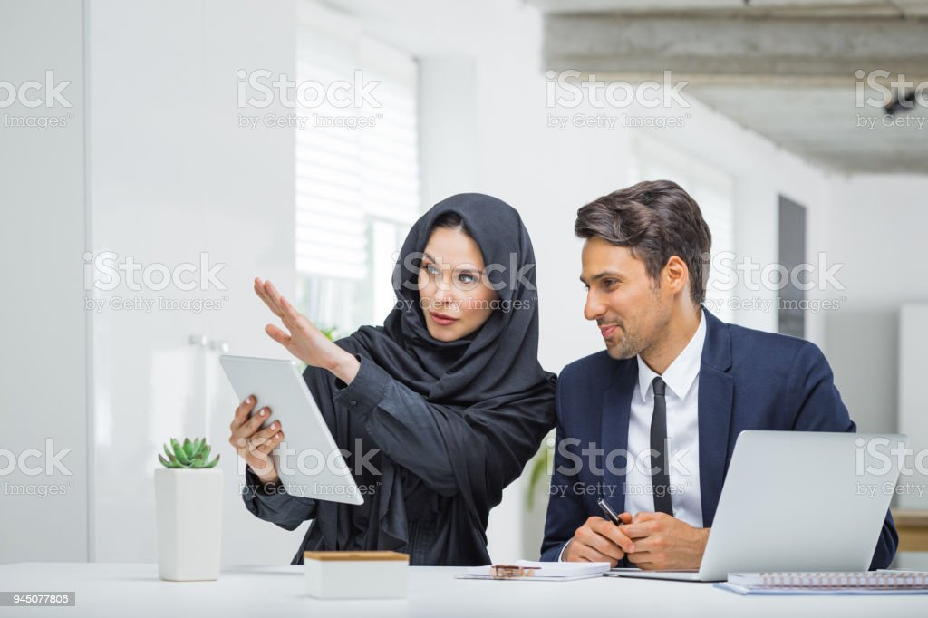 Business couple working together on project at startup office Business couple working together on project at startup office. Musilm businesswoman in hijab with male colleague looking at digital tablet. Adult Stock Photo