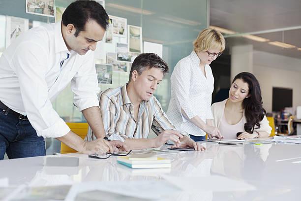 business coworkers collaborating at conference table in planning studio - oficina de empleo fotografías e imágenes de stock