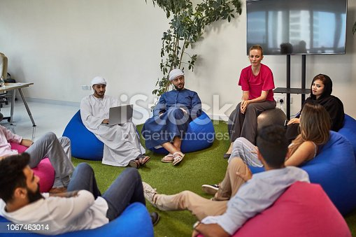 istock Business coworkers sitting on bean bags in meeting 1067463014