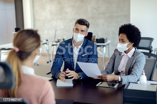 Members of human resource team wearing protective face masks while communicating with a candidate during job interview in the office.