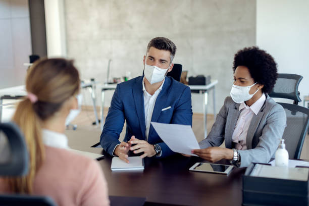 Business coworkers wearing face masks while talking to potential job candidate in the office. Members of human resource team wearing protective face masks while communicating with a candidate during job interview in the office. job interview stock pictures, royalty-free photos & images