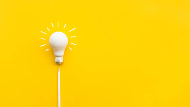 Business creativity and inspiration concepts with lightbulb and pencil on yellow background stock photo