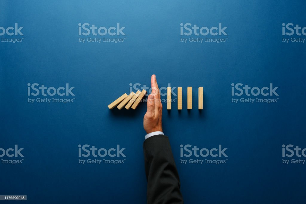 Business crisis management conceptual image Top view  of businessman hand stopping falling dominos in a business crisis management conceptual image. Assistance Stock Photo