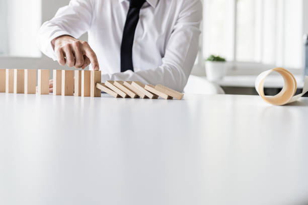 Business crisis manager stopping dominos from collapsing stock photo
