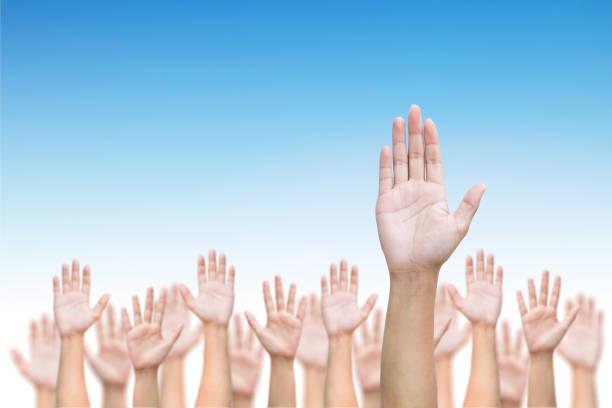 business crowd raising hands high up on blue skies background. - uwiedzenie zdjęcia i obrazy z banku zdjęć