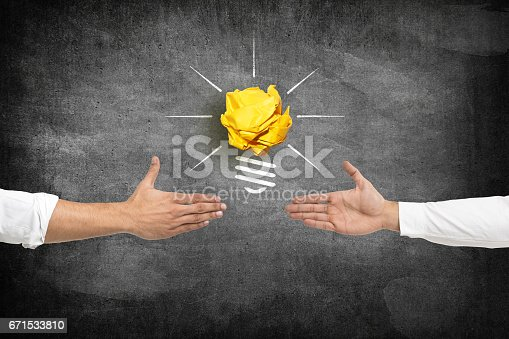 istock Business deal in front of light bulb icon with crumpled paper ball 671533810