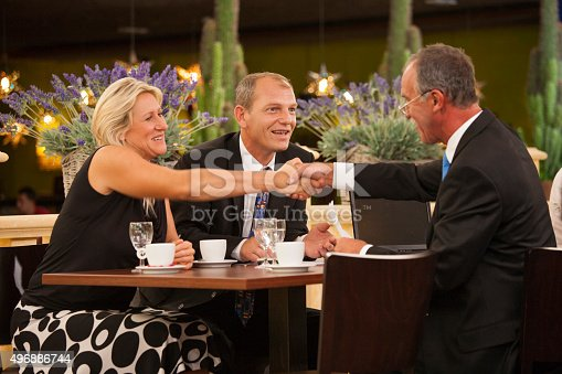 Business people having diner in an restaurant. One older man is presenting his ideas to a couple on the other side of the table. The deal is done and he is shaking hands with the woman. Laptop computer and drinks on the table. All businessman and businesswoman are smiling.