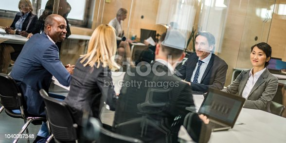 Two groups of business people sitting at opposite sides at a table and discussing a business deal.