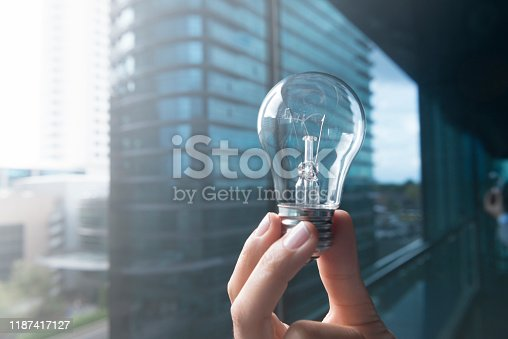 Hand is holding a light bulb with skyscraper view in the background.