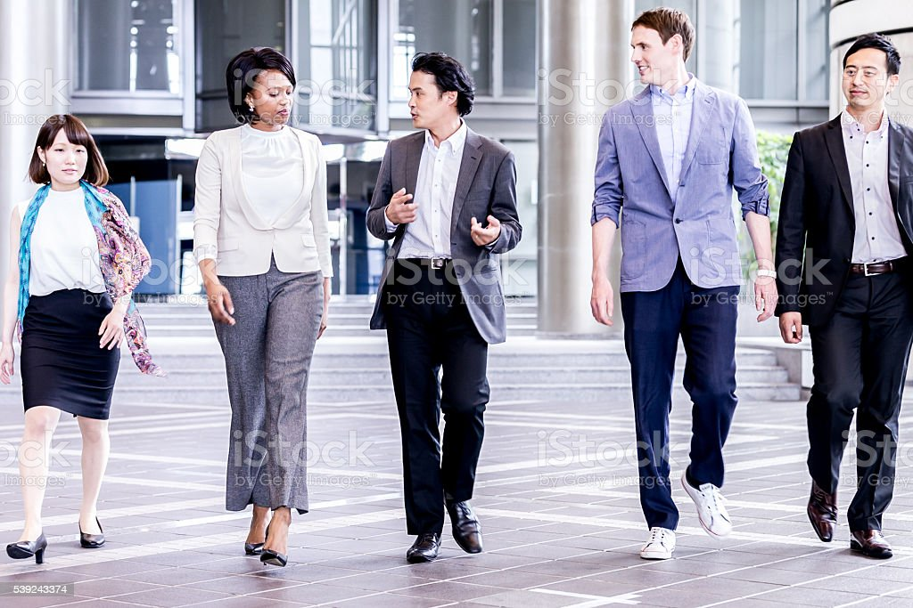 Business delegation walking out of convention center royalty-free stock photo