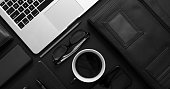 Business desktop concept. Mix of office supplies and gadgets on a black table background. With laptop, mobile phone, glasses, notebook, cup of coffee. View from above.