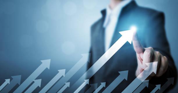 業務發展向成功和成長型發展的理念。商人指著箭頭圖企業未來增長 - 成功 個照片及圖片檔
