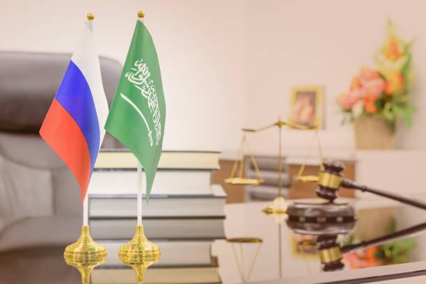 dialog zwischen wirtschaft, militär und öl-abkommen-konzept: nationalflaggen der russland und saudi arabien auf einem tisch. ein symbol der zusammenarbeit zwischen den zwei nationen, moskau / kreml und riad, einen islamischen staat - opec stock-fotos und bilder