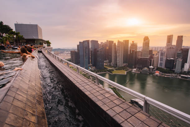 business district aerial view from infinite swimming pool of marina bay sands hotel. downtown landscape at golden sunset. travel luxury cityscape - marina bay sands stock photos and pictures