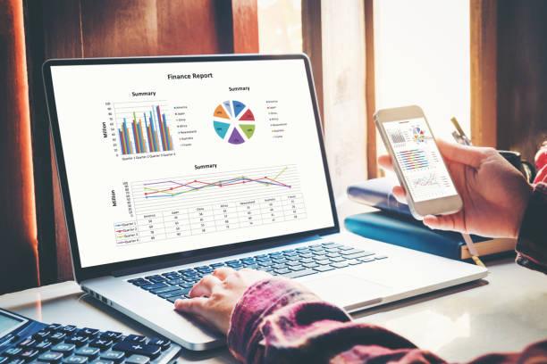 geschäftsdokumente auf büro mit smart handy und laptop-computer und grafik finanzielle mit sozialen netzwerk-diagramm und drei kollegen diskutieren daten im hintergrund - tabellenkalkulation stock-fotos und bilder